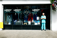 The proprietor of Leroy Menswear stand in the doorway and looks